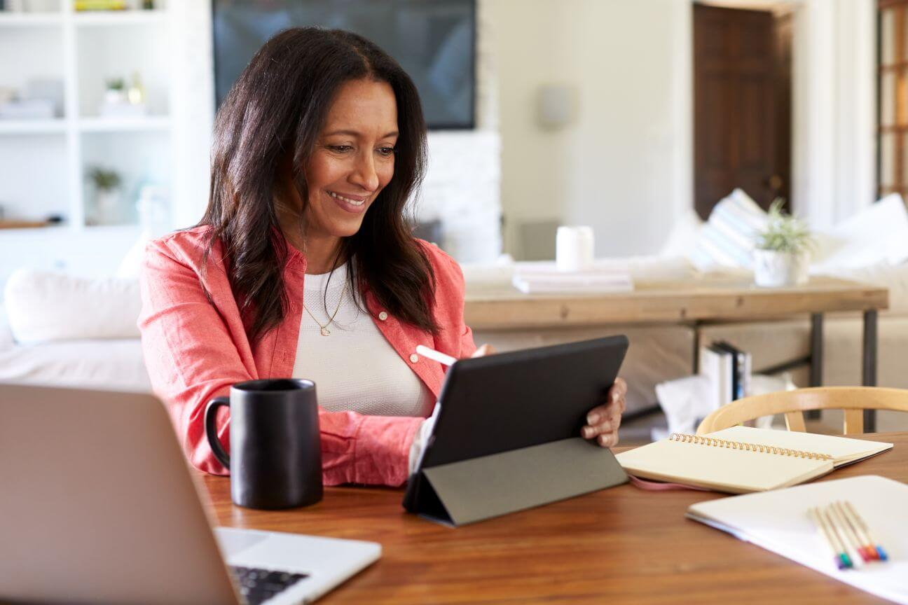 Empty nester at desk with tablet reflecting on God's calling for her life