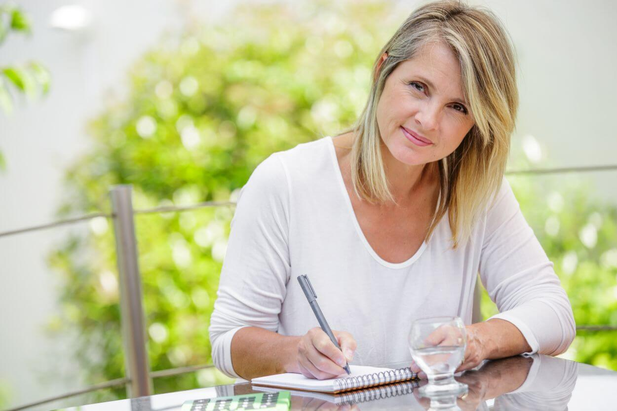 Woman in empty nest season writing God's calling for her life in notebook