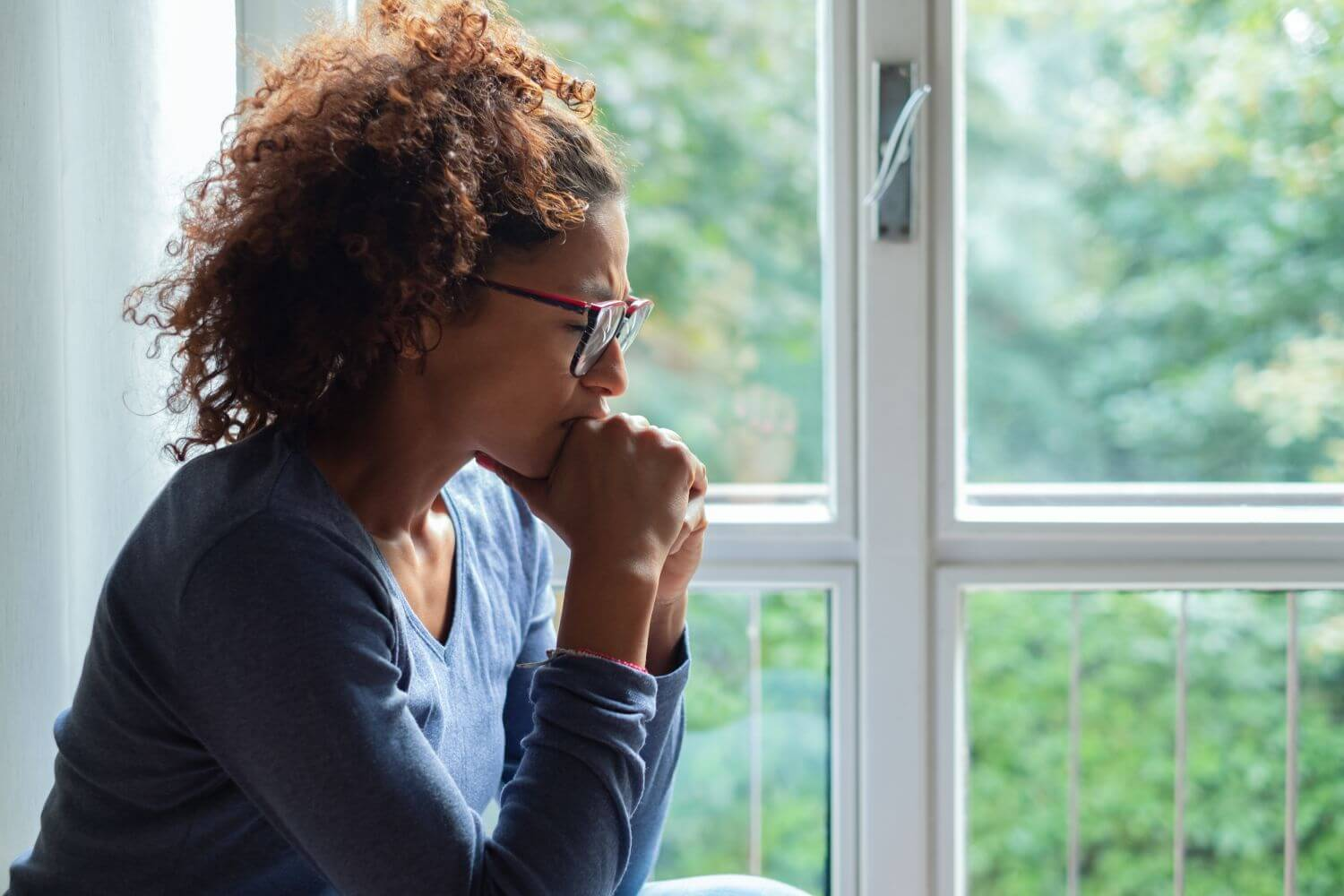 Empty nester by window pondering God's purpose for her life