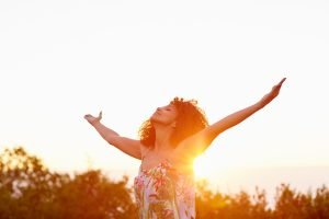 Christian woman lifting hands in praise for God's purposes