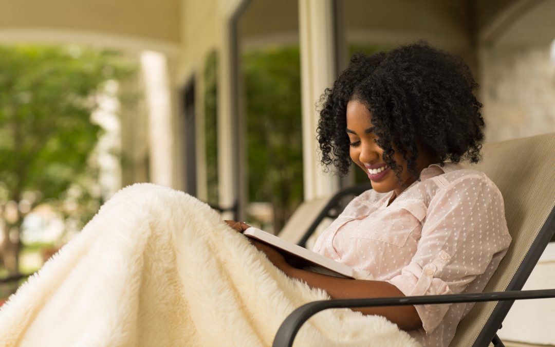 Woman in Christian Life Balance reading a book with blanket